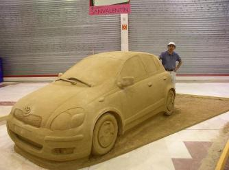 Life size sand sculpture of a car.