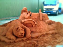 Sand sculpture of bear and tractor.