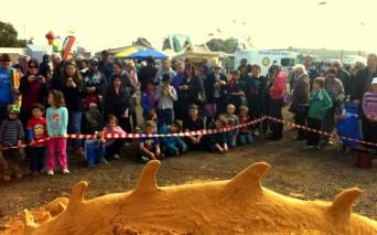 Crowds watching the sand becoming a dragon.