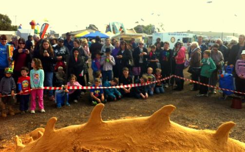 Crowds watching a sand sculpture at a festival.