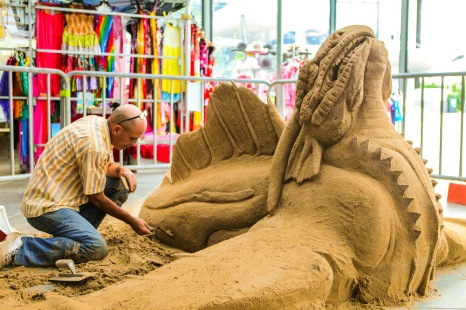Sand sculpting a sea monster.