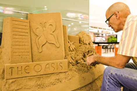 Logo and forest scene sand sculpture.