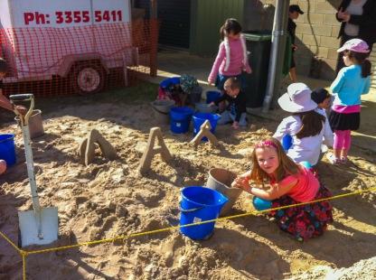 Children building sand sculptures of arches.